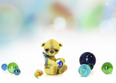 button does not like marbles (rockinmonique) Tags: button tinybear teddybear toy miniature tiny marbles highkey bokeh yellow blue green moniquewphotography canon canont6s tamron tamron45mm copyright2019moniquewphotography