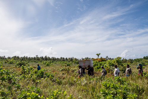 Islanders carry a box of humanitarian supplies from the air-drop site to their village center during OCD