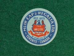 Muir (The Chairman 8) Tags: muir label circle muircapregalialtd round simcoest muircapregalialimited themuirbrand 1875 simcoestreet red lightblue darkblue blue felt green tornoto ontario canada