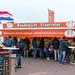 Passanten mit Winterkleidung essen an Imbissbude Boudewijns Visservice am Strand von Zandvoort, Niederlande