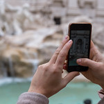 A woman takes a vertical photo with her iPhone at the Palazzo Venezia Garden in Rome thumbnail