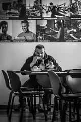 Dining with the Artists (tim.perdue) Tags: north market columbus ohio downtown urban city short arena district candid street black white bw monochrome nikon d5600 nikkor 18140mm dining with artists man person figure lunch table chair poster wall eating texting phone