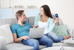 Happy couple with credit card sitting on sofa and making online shopping (haroldgrant) Tags: apartment background bank buy buyer card caucasian computer computering couch couple credit customer female happy home housewife indoors interior laptop living love making male man modern online paying pc people purchase purchasing room sale service shop shopaholic shopper sitting sofa table team together white woman young repair