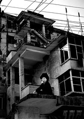 Woman Sitting On A Terrace Of A Modern Building, Yuanyang, Yunnan Province, China (Eric Lafforgue) Tags: a6795 asia blackandwhite buildingexterior china home house onepeople oneperson realpeople vertical yunnan yunnanprovince yuanyang