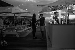 early evening at the Manly Pier Hotel, Sydney harbour, 2018  #616 (lynnb's snaps) Tags: street people bw slr film bar night lights hotel pub manly drinking apx100 rodinal umbrellas sydneyharbour lastlight nikonf80 manlywharf 2018 agfaapx100 afnikkor35mmf2d sydneypubs manlypierhotel ©copyrightlynnburdekinallrightsreserved ishootfilm