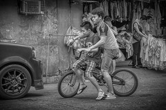 Just Do it 2 (Beegee49) Tags: street black white monochrome bw boys teens bicycle cycling two up happy planet riding market skylum bacolod city philippines asia sony a6000