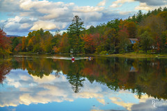 Autumn Reflections in a Vermont Lake (RobertCross1 (off and on)) Tags: a7rii alpha emount fe85mmf18 ilce7rm2 ludlow newengland sony vt vermont windsor autumn boats canoe clouds fall foliage forest fullframe house lake landscape leaves mirrorless reflection trees water