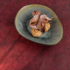 Chocolate profiterole (annick vanderschelden) Tags: profiterole creampuff chouˆlacrme filled french chouxpastry ball sweet moistfilling whippedcream custard pastrycream decoration chocolatesauce powderedsugar savory chocolateganache food dessert sugar icingsugar rose golden plate chouàlacrème