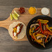 The ingredients for the hellofresh receipt: vegan fajitas with peppers, mushrooms, hot sauce and lime-cream on a cutting board - top view