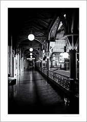 Derby market hall, upper level (G. Postlethwaite esq.) Tags: bw derby derbyshire fujix100t arches blackandwhite chair lamps markethall monochrome photoborder pillars sign table