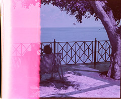 Imperfetto (ale2000) Tags: 35mm lomography newpurple400 purple sicilia sicily analog analogphotography analogue film firstoftheroll fotografiaanalogica pellicola shiftedcolors viola lomochrome ql19 newlomochromepurple400 filmisnotdead believeinfilm shifted colorshifting people streetphotography santostefanodicamastra sight view vista terrazza sea summer estate bench panchina frombehind