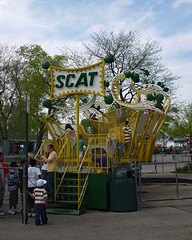 Scat Carnival Ride. (dccradio) Tags: greenbay wi wisconsin browncounty baybeach amusementpark park fuji finepix a900 carnival midway fairride amusements amusementdevice mechanicalride ride rides thrillride outdooramusement fun entertainment outdoors outside tree trees greenery springtime leaf leaves treebranch branch branches treebranches outdoor venturerides groverwatkins watkins scat hiliterides sky clouds bluesky sign words text people trashcan garbagecan fence concrete chainlinkfence steps stairs
