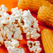 Heads of corn and popcorn on orange background
