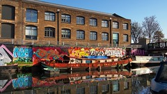 The view from Hackney Wick - looking east across 'River Lea Navigation', Tower Hamlets, London .. (edk7) Tags: olympusomdem5 edk7 2018 uk england london londonboroughoftowerhamlets hackneywick riverleanavigation canal warehouse factory architecture building oldstructure boat ship narrowboat rust crusty crust bridge sky tree graffiti wallart mural city cityscape urban