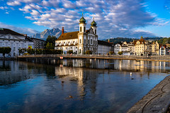 A early morning view of the Jesuit Church in Lucerne Switzerland (pa_cosgrove) Tags: red lucerne switzerland water river relfections reflections jesuit church morning mountians clouds bridge sony a73