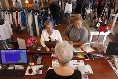 Merchant helps two customers, Joy Simpson (left) and Haley Simpson (right) with a transaction. The women have a hunting farm in Greene County, and they were shopping while Joy Simpson's husband was turkey hunting.