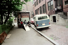 71-100 (ndpa / s. lundeen, archivist) Tags: nick dewolf nickdewolf color photographbynickdewolf 1975 1970s film 35mm 71 reel71 boston massachusetts beaconhill dewolfhome 3mtvernonsquare truck movingtruck uhaultruck vw volkswagen bus microbus car vehicle automobile ford mustangii mustang children kids child boy boys ivan pierre teddypierre cobblestone curb sidewalk building steps stairs door windows house houses architecture fence chainlinkfence furniture loadedtruck load themove moving boxes ramp men youngmen man youngman denim jeans relaxing summer july