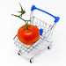 A tomato in a miniature shopping cart