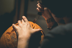 Master Craftsman (music_man800) Tags: knife blade cut skill master craftsman craft art make create carve carving pumpkin pumpkins kitchen halloween american uk united kingdom essex southend fall autumn 2018 dark moody mood tattoo wrist person concentrate arty artistic atmospheric eerie hand hands handy woman home house indoors evening night canon 700d adobe lightroom creative cloud edit photography 50mm prime lens shade shadows contrast orange light lighting bulb