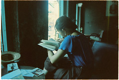 (grousespouse) Tags: vietnam 35mm analog film kodakvision200t tungsten cinema cinematic colorfilm analogue blue grain mood fade indoors cafe hoian girl portrait reading vietnamese croplab grousespouse 2018 nikonf3 nikonseriese 28mm f28 wideangle vision3