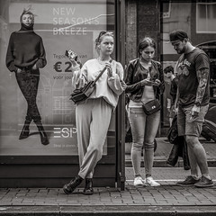 waiting for the tram (Gerard Koopen) Tags: nederland netherlands amsterdam capital city urban straat street straatfotografie streetphotography bw blackandwhite blackandwhiteonly noir streetportrait streetlife people woman women man tattoos poster fashion streetfashion sonyalpha a7iii beautiful 2018 gerardkoopen gerardkoopenphotography