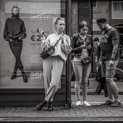 waiting for the tram (Gerard Koopen) Tags: nederland netherlands amsterdam capital city urban straat street straatfotografie streetphotography bw blackandwhite blackandwhiteonly noir streetportrait streetlife people woman women man tattoos poster fashion streetfashion sonyalpha a7iii beautiful 2018 gerardkoopen gerardkoopenphotography