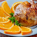 Fried duck leg with oranges on a white plate close-up
