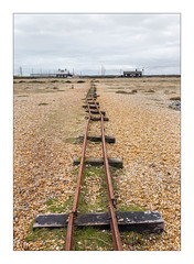 Abandoned Narrow Gauge Railway Lines, Dungeness, Kent, England. (Joseph O'Malley64) Tags: dungenessbeach dungeness kent england uk britain british greatbritain coast coastal seaside thebritishseaside expanse desolate desolation gravel shingle narrowgaugerailway railwaylines sleepers grasses bungalows housing homes dwellings abodes powerlines nationalgrid nationalgridpowerlines abandoned neglected derelict dereliction pylons electricitypylons telephonelines landscape fujix fujix100t accuracyprecision documentaryphotography britishdocumentaryphotography thebuiltenvironment newtopography newtopographics manmadeenvironment manmadestructures