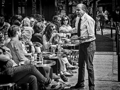 Waiter at the end of his tether (Jan Kranendonk) Tags: paris france french parisian buildings architecture sunny sky blue montmartre people travel street urban corner ruedelapepiniere pavement sitting tables restaurant cafe cafetaria table chairs waiter