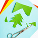 Colorful craft paper with christmas tree cutout and scissors on white background