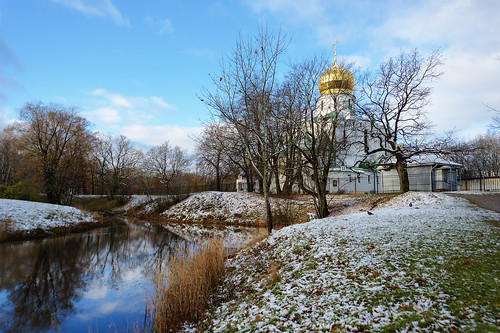 First snow. Cathedral on the shore of the blue lake.