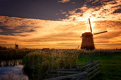 The Fire Behind The Windmills (Alfred Grupstra) Tags: sunset nature landscape windmill sky dusk sun sunlight sunrisedawn ruralscene summer outdoors scenics cloudsky water grass tranquilscene beautyinnature field
