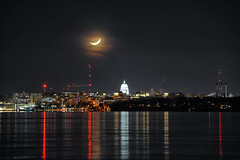 Lined Up (Kirby Wright) Tags: long exposure telephoto moon crescent capitol isthmus downtown madison wisconsin dane county orange glow light trails reflection nikon d700 80200mm f28 manfrotto tripod skyline city building cranes clouds thin