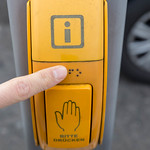 Sehbehinderter Fußgänger liest Blindenschrift an gelbem Druckknopf für Ampelanlage in Köln thumbnail