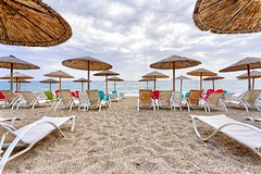 Summer memories: Waiting for the sun (bbarekas) Tags: beach umbrellas sunbeds sand sky clouds sea chairs colors cloudy day windy 17mm hdr 3shots summer landscapemonolithi preveza epirus greece