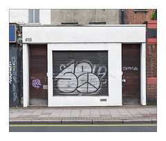The Built Environment, East London, England. (Joseph O'Malley64) Tags: thebuiltenvironment newtopography newtopographics manmadeenvironment manmadestructures buildings structures architecture architecturalfeatures architecturalphotography urban urbanlandscape britishdocumentaryphotography documentaryphotography graffiti tags stickers businesspremises shop shopfront frontage victorian victorianbuilding modernised renovated brickwork bricksmortar cement pointing render shutter rollershutter doorways doors woodenpanelleddoors entrances exits lamp lighting junctionbox wiring electricalwiring keypadentrysystem intercomsystem blockpaving pavement granitekerbing tarmac singleyellowline parkingrestrictions fujix fujix100t accuracyprecision 410