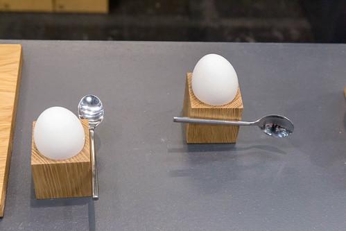 Hölzerner quadratischer Eierbecher mit eingebautem Magnet und davon gehaltenem Löffel