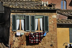 Drying in the Tuscan sun - residential district, Siena. (edk7) Tags: nikond300 nikonnikkor18200mm13556gedifafsvrdx edk7 2008 italy italia tuscany toscana siena contradadellondadistrict contradadellonda architecture building oldstructure old city cityscape urban centre rooftile ceramic wall shadow window stonework brick crusty texture pattern lichen shutter chimney blanket clothes clothing clothesline
