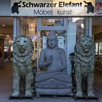 Eine Buddhastatue und Löwenstatuen vor einem Möbelgeschäft thumbnail