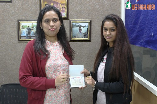 Ms. Parwinder Kaur (Director of West Highlander) handing over Canada Student Visa to Vishavpreet Bhasin