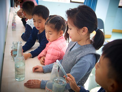 2019 Winter Camp Science Lesson 03 (ArdieBeaPhotography) Tags: boys girls children kids little young middleschool elementaryage schoolholiday programme class group classroom bench table chair window bottles water markers felttippens winter jacket jeans tights puffy pullover sweater jersey jumper strike hit musical vibrate vibrations science lesson teach learn friends ponytail long black hair sweet pretty patterned lean whisper listen ring pour level laugh fun tamronspaf2875mmf28xrdildasphericalif noise