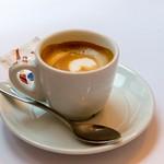 Espresso mit kräftiger Kaffeecrema in weißer Tasse mit Löffel und Zucker thumbnail