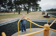 henry at play, part two (manyfires) Tags: nikonf100 35mm analog film boy son toddler henry family love child portrait peoplescape play fun cihldhood bandon oergon oregoncoast merrygoround playground spin