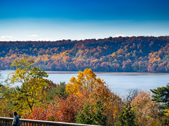 The Passing of Autumn (Mildred Alpern) Tags: autumn trees hudsonriver figure wall sky colors leaves