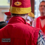 Mann von hinten mit Hut in den Farben der Deutschlandflagge und roter Weste mit der Aufschrift Hutbürger, im Hintergrund weitere Personen mit gleicher Bekleidung thumbnail