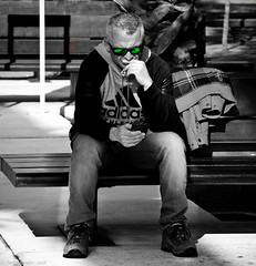 The green-eyed monster (Neil. Moralee) Tags: neilmoralee spainneilmoralee man sitting glasses sun sunnies shades green eye eyed monster jelousy othello sunshine shadow black white mono monochrome blackandwhite bw bandw street candid spain malaga eyd beast phone mobile text txt message trust neil moralee nikon d7200 torture reflection