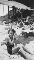 Relaxing in the shade of an umbrella at Coolangatta Beach, ca. 1934 (State Library of Queensland, Australia) Tags: queensland statelibraryofqueensland bathingbeauties swimmingcostume women womensfashion womensclothingaccessories umbrella beachtowel beach beachumbrella