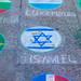 Die Israelische Flagge mit Münzen auf dem Boden auf dem Platz des Kölner Weihnachtsmarktes