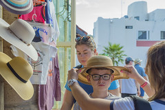Hat Shopping in a Market in Cabo San Lucas (aaronrhawkins) Tags: shopping tourist hat shop market boy unhappy cabosanlucas funny clothes display vacation joshua kellie jessica family aaronhawkins mexico