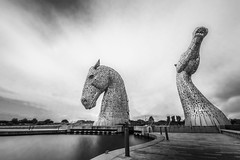 "long exposure black & white of the magnificent horse heads - The Kelpies, Falkirk, Scotland (grumpybaldprof) Tags: canon 7d ""canon7d"" sigma 1020 1020mm f456 ""sigma1020mmf456dchsm"" ""wideangle"" ultrawide bw blackwhite ""blackwhite"" ""blackandwhite"" noireetblanc monochrome ""fineart"" ethereal striking artistic interpretation impressionist stylistic style contrast shadow bright dark black white illuminated mood moody atmosphere atmospheric ""thekelpies"" horsehead sculpture forth clyde canal ""rivercarron"" ""thehelix"" scotland uk ""andyscott"" statues 2013 ""forthclydecanal"" ""riverforth"" steel ""stainlesssteel"" ""30mtall"" ""300tonnes"" art artist mythology ""heavyhorse"" longexposure nd neutraldensity filter"